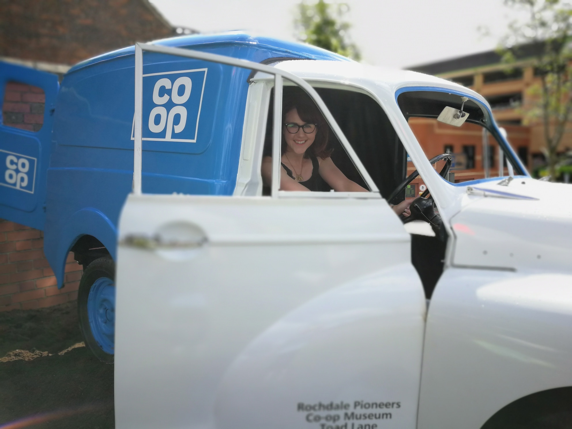 female sitting in a 1970s co-op delivery van