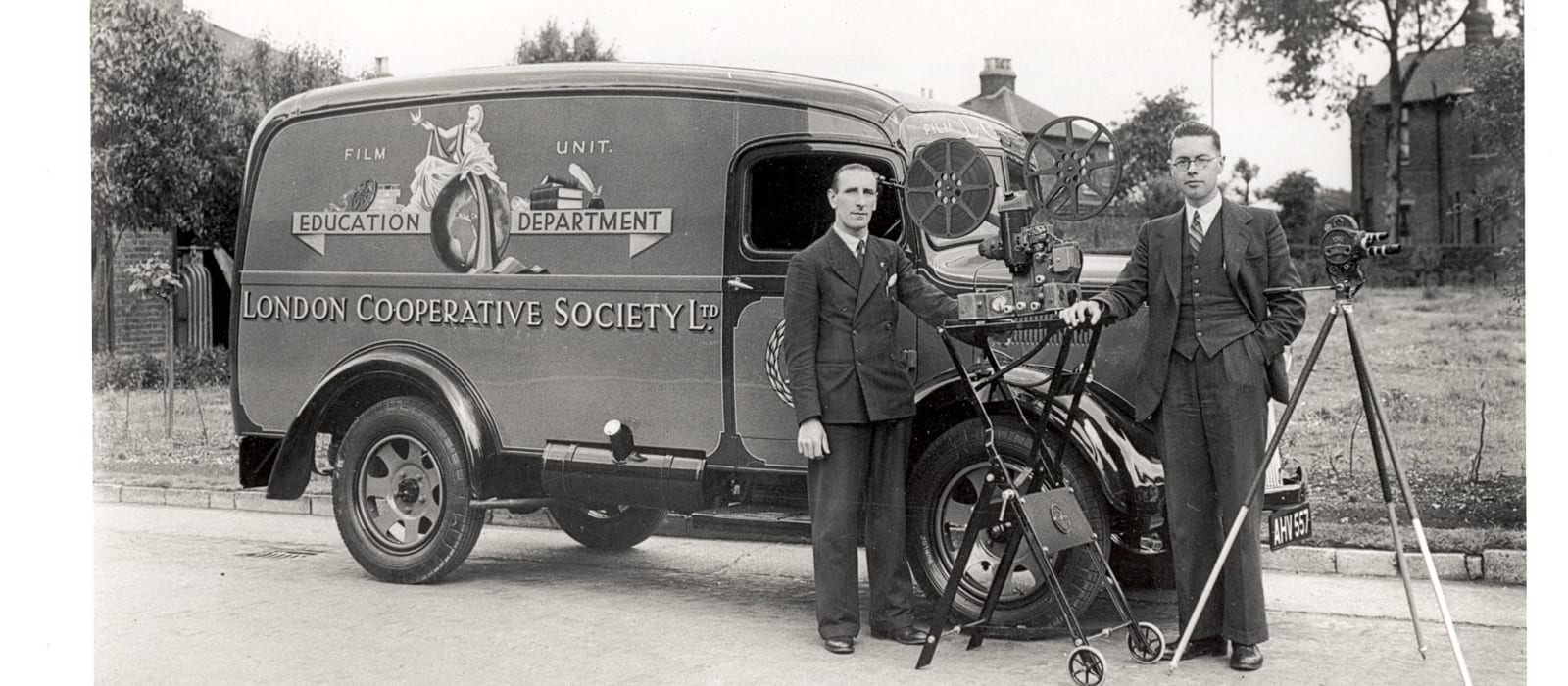 Image of the Co-operative education film department van and two men with film camera in the 1940s.